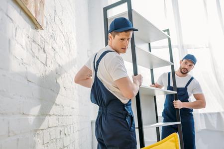 deux déménageurs en rack de transport uniforme dans un appartement avec espace de copie