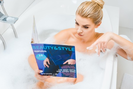 selective focus of attractive and blonde woman taking bath with foam and pointing with finger at beauty and style magazine