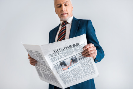 selective focus of mature businessman reading business newspaper isolated on grey 스톡 콘텐츠