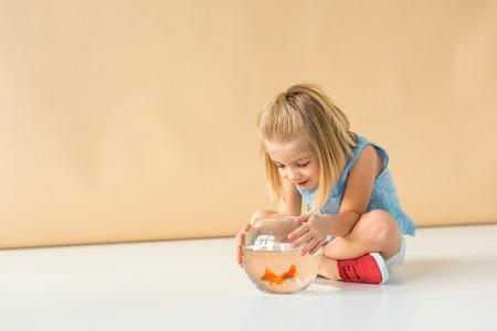 entzückendes Kind, das mit gekreuzten Beinen sitzt und Goldfischglas auf beigem Hintergrund betrachtet