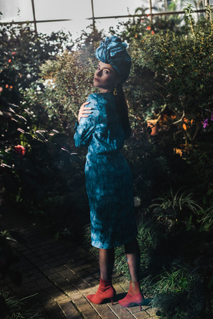 Full length view of attractive woman in blue dress and turban in orangery