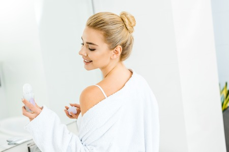 blonde and smiling woman in white bathrobe holding deodorant in bathroom Archivio Fotografico