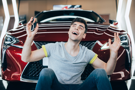 happy excited man sitting near new car in car showroom 免版税图像