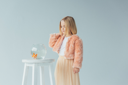 cute kid in faux fur coat and skirt looking at fishbowl on stool isolated on grey