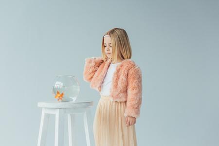 süßes Kind in Kunstpelzmantel und Rock mit Blick auf Goldfischglas auf Hocker isoliert auf Grau Standard-Bild