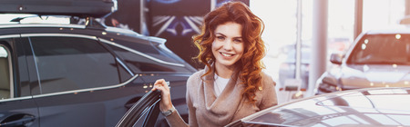 panoramic shot of happy curly woman smiling while standing near vehicle in car showroom Stock Photo