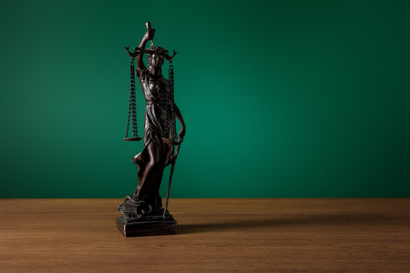 bronze statuette with scales of justice on wooden table on dark green background Stock Photo
