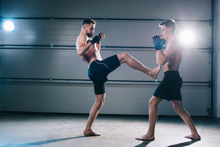 side view of muscular barefoot mma fighter kicking opponent with leg Imagens