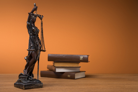 selective focus of bronze statuette with scales of justice and volumes of brown books on table