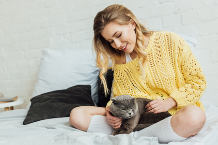beautiful smiling girl in knitted sweater stroking scottish fold cat while lying in bed at home 写真素材