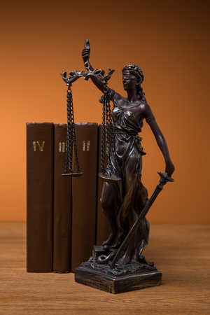 bronze statuette with scales of justice and row of brown books on wooden table Stock Photo