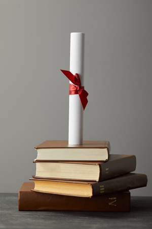 Diploma with red ribbon and books on textured surface isolated on grey