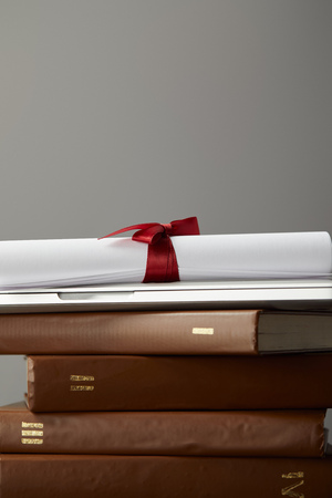 Brown books, laptop and diploma with red ribbon isolated on grey Stockfoto