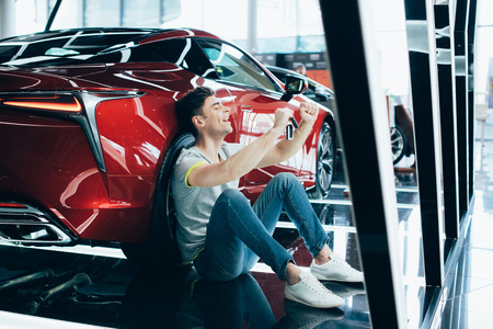 selective focus of happy man sitting on floor near new red car and showing yes gesture Stock Photo