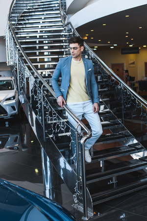 stylish man in glasses walking down stairs in car showroom