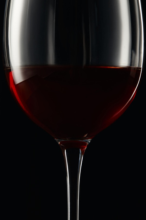 Glass of burgundy red wine isolated on black 写真素材