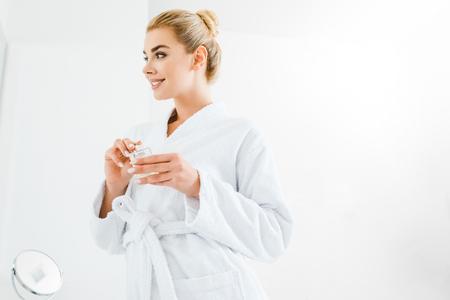 beautiful and smiling woman in bathrobe holding perfume in bathroom