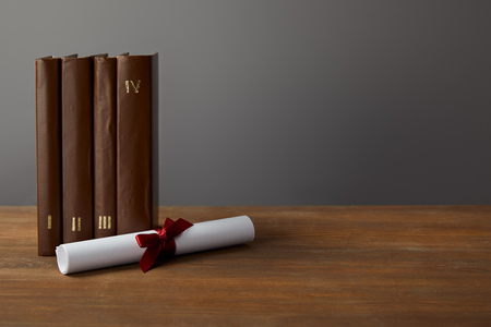 Brown books and diploma with red ribbon on wooden surface on grey