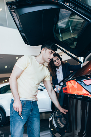 selective focus of handsome man and car dealer standing near new car Stock Photo