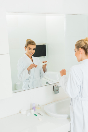 woman in bathrobe applying toothpaste on toothbrush and looking at mirror