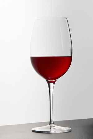 Wine glass with red wine on dark surface on white Stok Fotoğraf