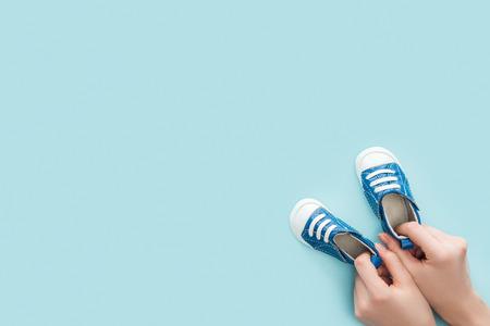 Vista parcial de mujer adulta sosteniendo zapatillas sobre fondo azul con espacio de copia Foto de archivo