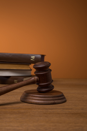 selective focus of volumes of brown books in leather covers and gavel on wooden table on dark orange background