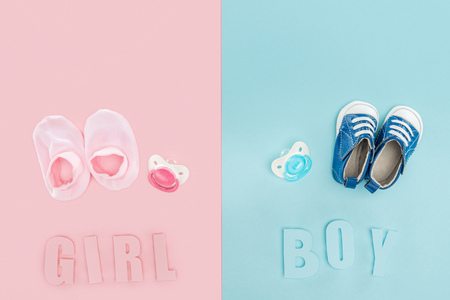 top view of pacifiers, booties, sneakers and boy, girl lettering Banque d'images - 120181101