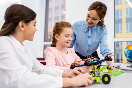 Professeur souriant debout près des élèves avec des jouets éducatifs en classe