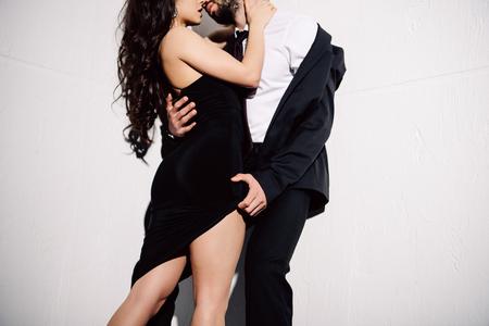 przycięty widok brunetki całującej się z mężczyzną na białym