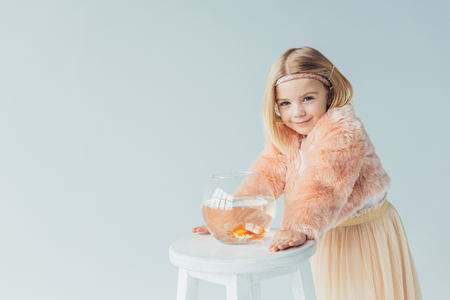 cute kid in faux fur coat and skirt with fishbowl looking at camera isolated on grey Standard-Bild