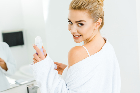 blonde and smiling woman in white bathrobe holding deodorant and looking at camera