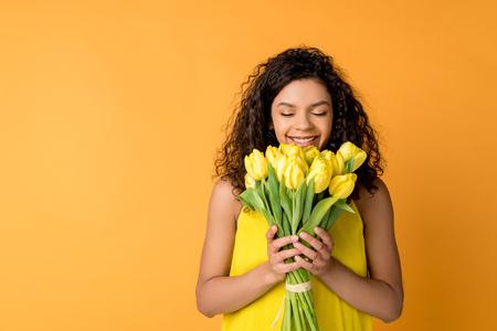 happy curly african american woman smelling yellow tulips isolated on orange