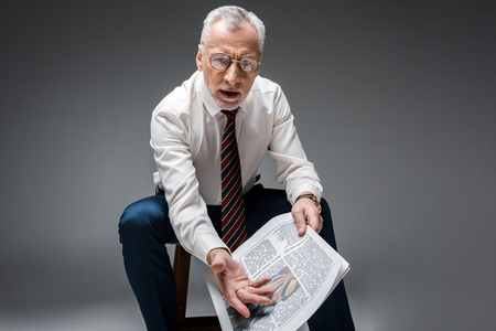mature businessman gesturing while holding newspaper on grey