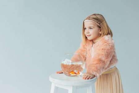 cute kid in faux fur coat and skirt with fishbowl looking away isolated on grey