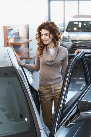 cheerful curly woman standing near vehicle in car showroom Stock Photo