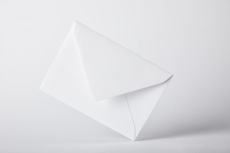white and empty envelope on grey background with copy space