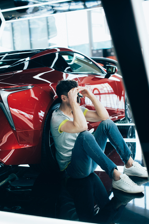 upset man sitting near red automobile in car showroom