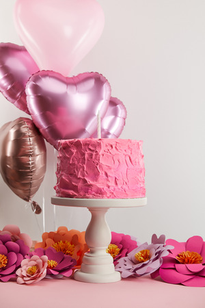sweet pink birthday cake with candle on cake stand near paper flowers and heart-shaped air balloons on grey Stockfoto