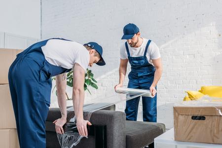 Déménageurs enveloppant le canapé avec un rouleau de film étirable dans l'appartement