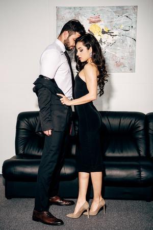 schöne Frau im schwarzen Kleid Mann im Anzug in der Nähe des Sofas ausziehen