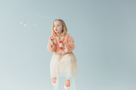 adorable kid in faux fur coat and skirt sitting on highchair and blowing soap bubbles isolated on grey