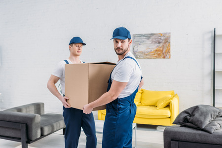 two handsome movers in uniform transporting cardboard box in apartment