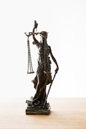 bronze statuette with scales of justice on wooden surface isolated on white