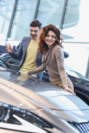 selective focus of cheerful curly woman smiling near excited man in glasses looking at car Stock Photo