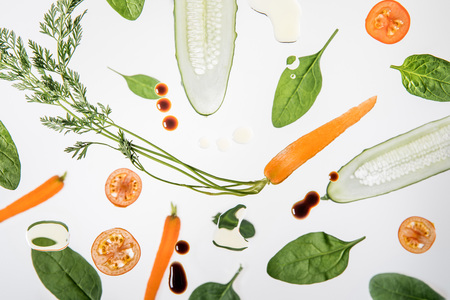 seasonal ripe sliced vegetables on grey background with water bubbles and sauce drops