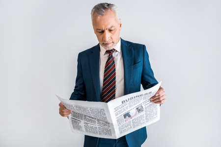 mature man in suit reading business newspaper while standing isolated on grey