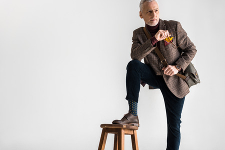 stylish mature man putting leg on chair while standing and holding glasses on grey