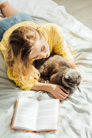 high angle view of beautiful young woman lying in bed with scottish fold cat and book Фото со стока