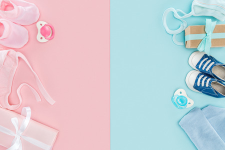 top view of pacifiers, gifts, hat, booties, sneakers, bonnets on pink and blue background